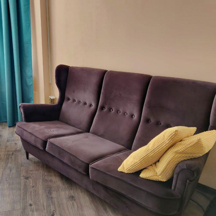 Уютный диван с высокой наклонной спинкой и ушами